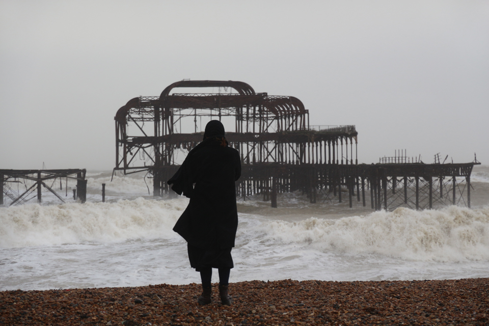 The object in the background is the Brighton old pier. Huge storms a few days ago caused part of the structure to collapse and people were waiting for the remaining ironwork to fall into the sea. It didn't.